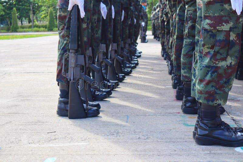 军事小组,战士的腿,是站在队中和拿着枪整洁地和与室外力量 免版税库存照片