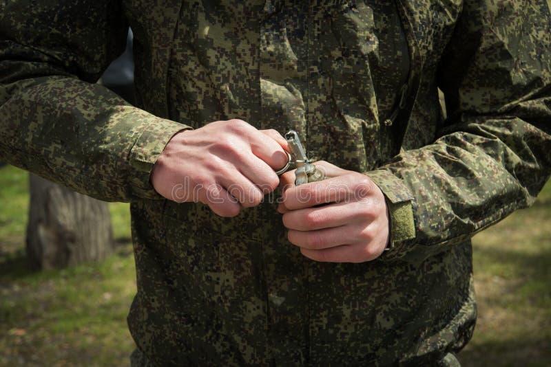 军事手榴弹投掷,拉扯 自爆炸 战士的手拉扯别针 库存图片