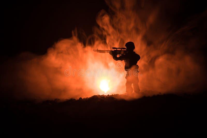 军事狙击手剪影有狙击手枪的在黑暗的被定调子的有雾的背景 射击,拿着枪,五颜六色的天空,背景 免版税库存图片