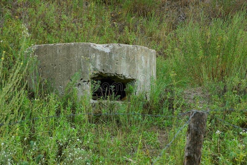 军事药盒的老发射孔在草的在铁丝网后 免版税库存图片