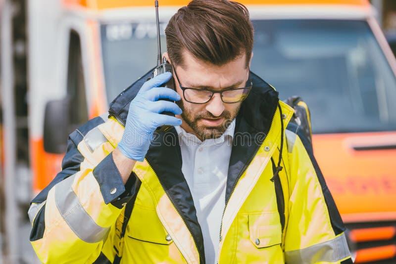 军医谈话与总部通过在救护车前面的收音机 免版税库存照片