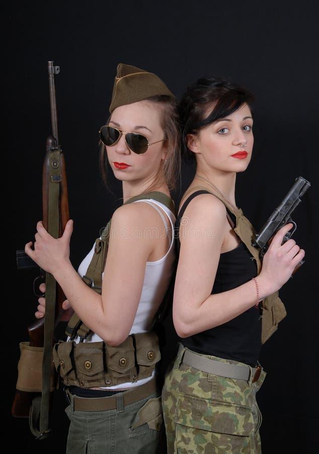 军服的两个相当少妇有枪的 图库摄影