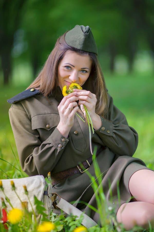 军服的女孩在领域坐拿着花束的草 库存图片