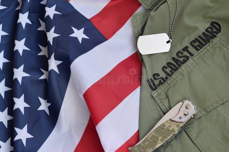 军犬标牌和刀位在美国海岸警卫队旧制服上,并折叠美国国旗 免版税库存图片