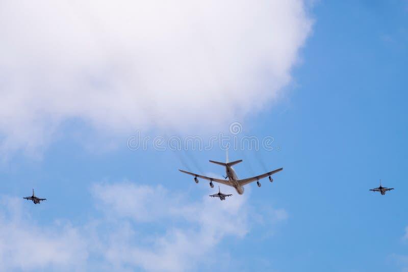 军用加油机refueler和喷气式歼击机在天空蔚蓝飞行 免版税库存图片
