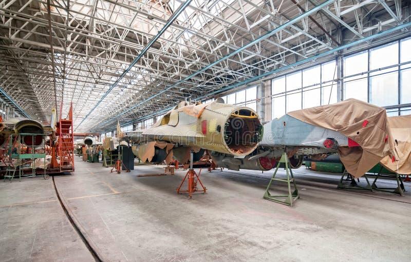 军用飞机的航空工厂 俄国战斗机的装配 在驾驶舱的焦点 免版税库存图片