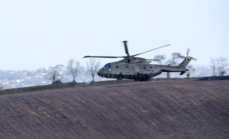 军用直升机在飞行中在农田英国 免版税库存照片