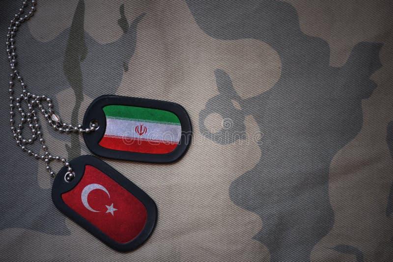 军队空白、卡箍标记与伊朗的旗子和火鸡在卡其色的纹理背景 免版税库存图片