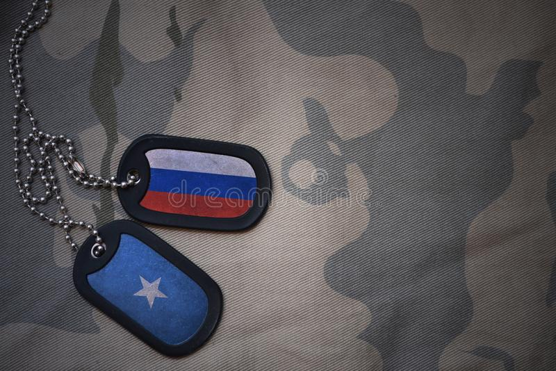 军队空白、卡箍标记与俄罗斯的旗子和索马里卡其色的纹理背景的 图库摄影