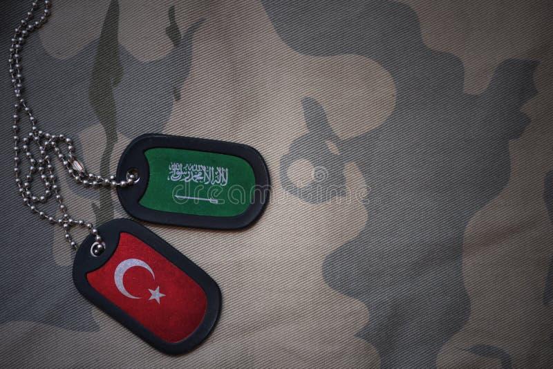 军队空白、卡箍标记与沙特阿拉伯的旗子和火鸡在卡其色的纹理背景 库存图片