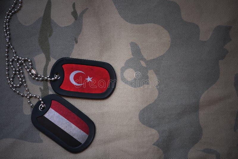 军队空白、卡箍标记与火鸡旗子和也门卡其色的纹理背景的 库存图片