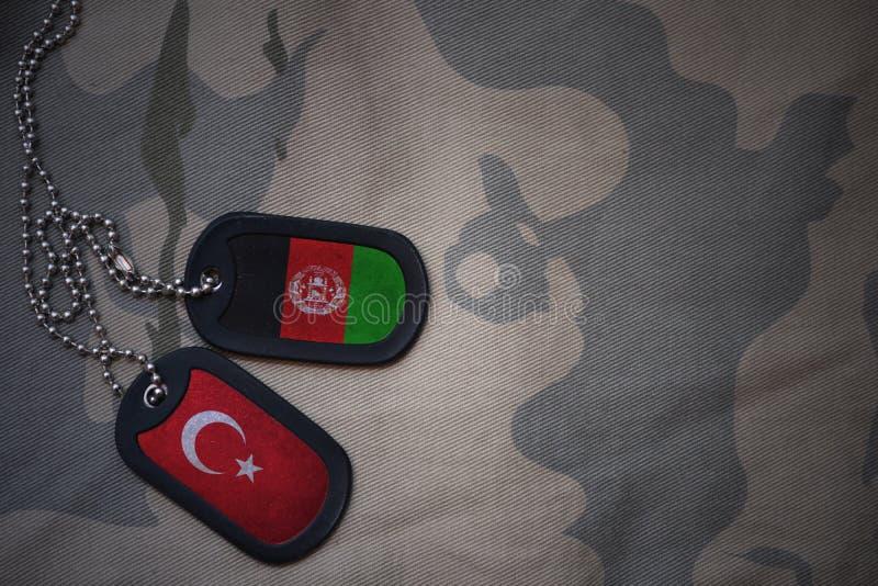 军队空白、卡箍标记与火鸡旗子和阿富汗卡其色的纹理背景的 库存图片