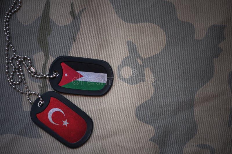 军队空白、卡箍标记与约旦的旗子和火鸡在卡其色的纹理背景 免版税图库摄影