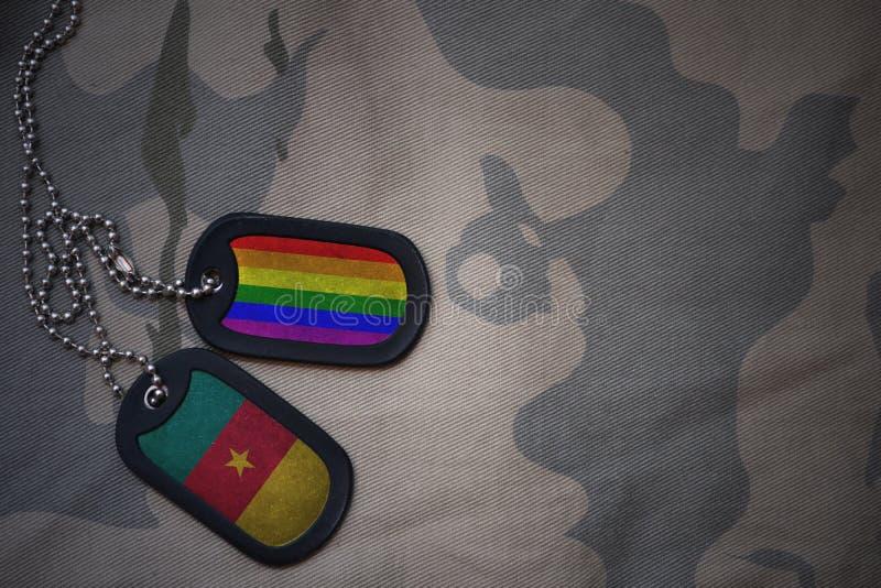军队空白,与喀麦隆的旗子和快乐彩虹旗子的卡箍标记在卡其色的纹理背景 库存照片