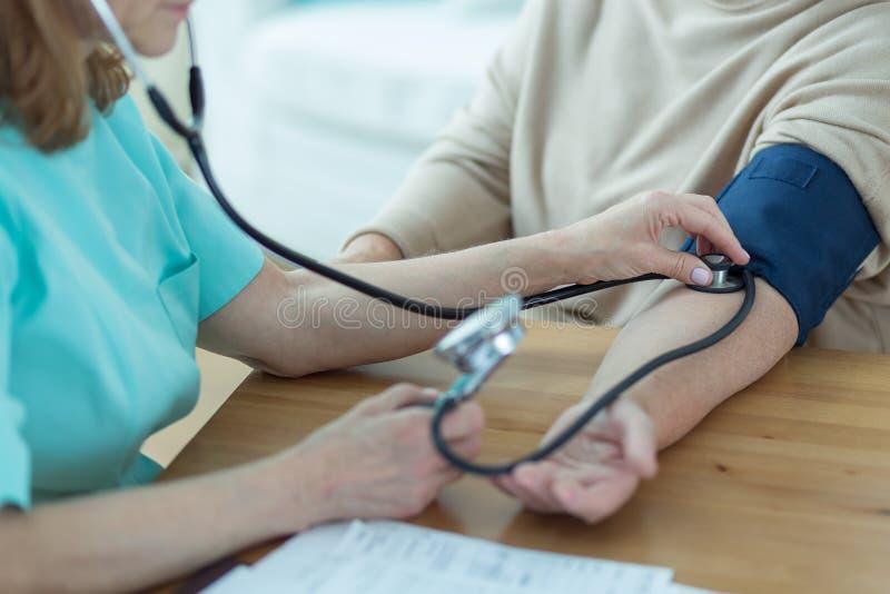 军医测量的血压 免版税库存图片
