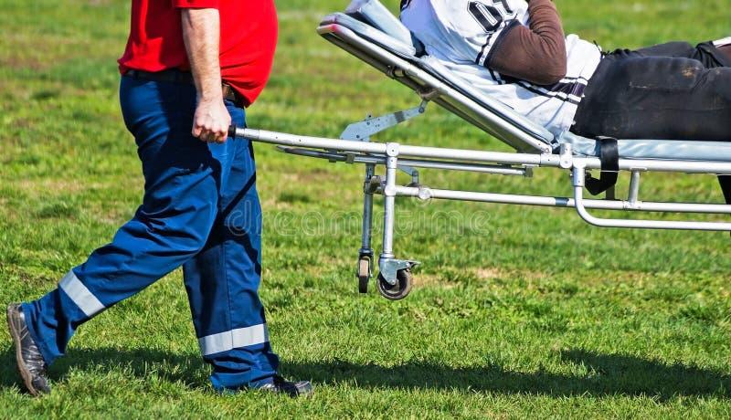军医运载受伤的足球运动员 免版税库存照片