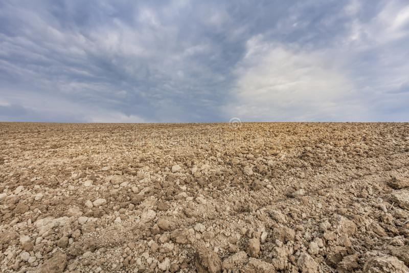 农业土壤空的农田领域和云彩天空背景 库存图片