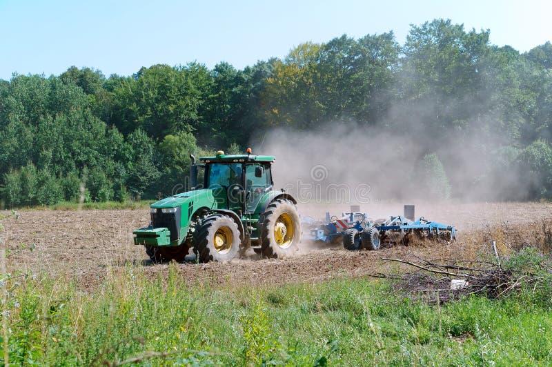 农业机器运转在领域的,犁土地的拖拉机 库存图片