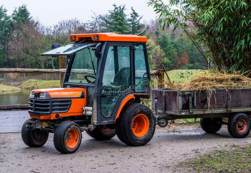 农业设备,有充满干草的拖车的橙色拖拉机,农业机械 库存图片