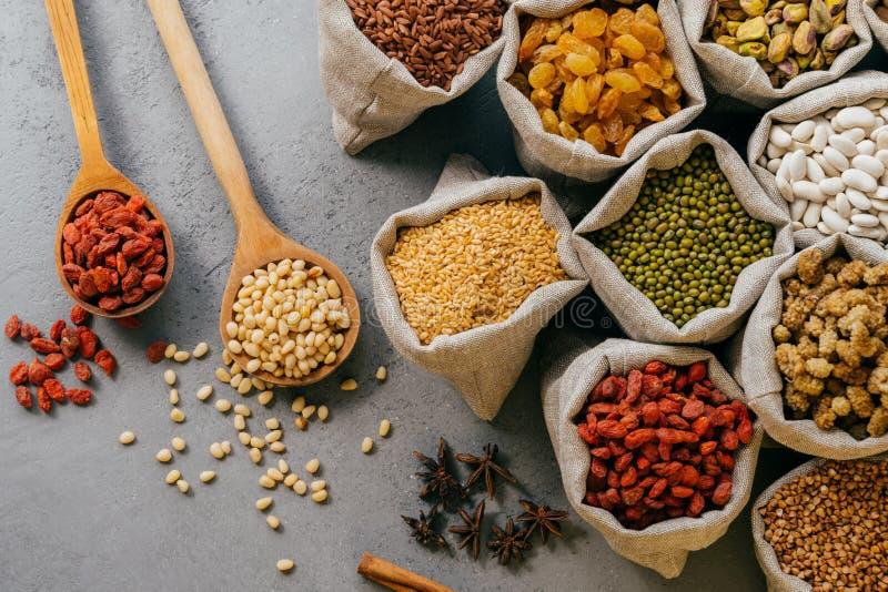 农事和nutrtion概念 在小的粗麻布大袋包装的各种各样的豆和五颜六色的干果顶视图  木匙子 免版税库存图片