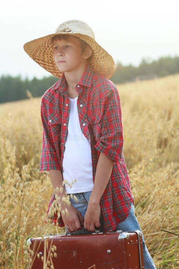 农厂拿着古板的手提箱和看对天际的燕麦领域的少年旅客 免版税图库摄影