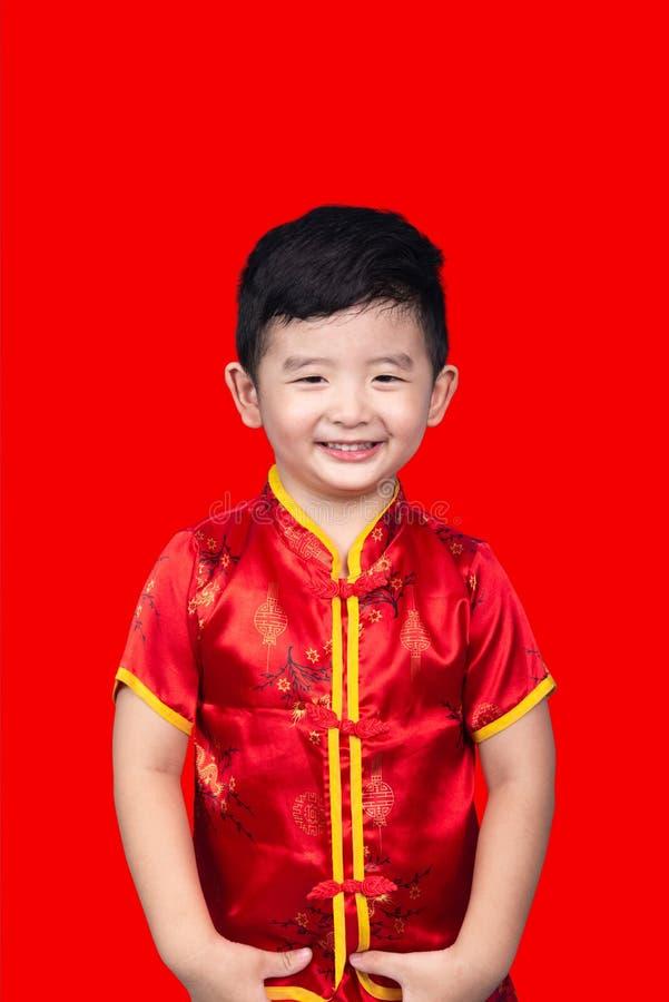 农历新年概念,在与裁减路线的红色隔绝的红色传统中国衣服的逗人喜爱的亚裔男孩 图库摄影