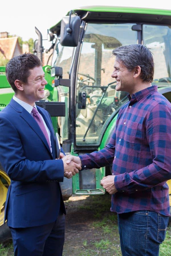 农夫和商人与拖拉机握手在背景中 免版税库存照片