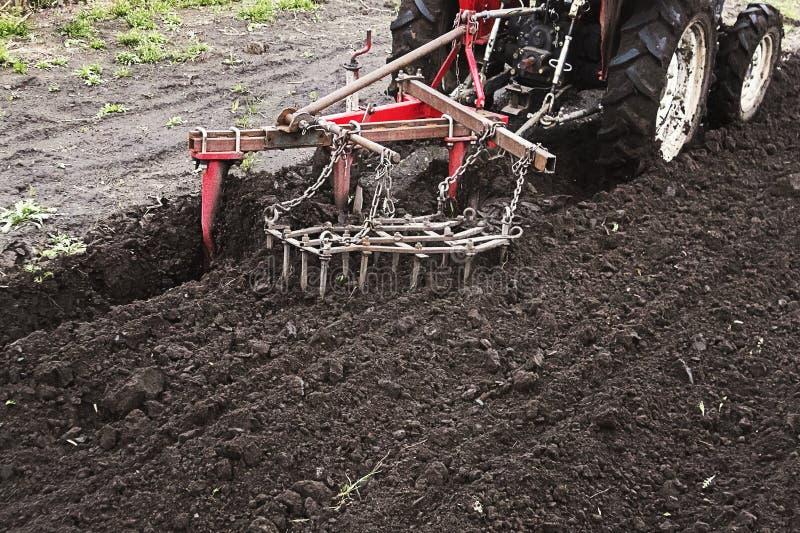 农夫土地为播种做准备 运转在农场,现代农业运输的拖拉机,运作在领域,肥沃土地 图库摄影