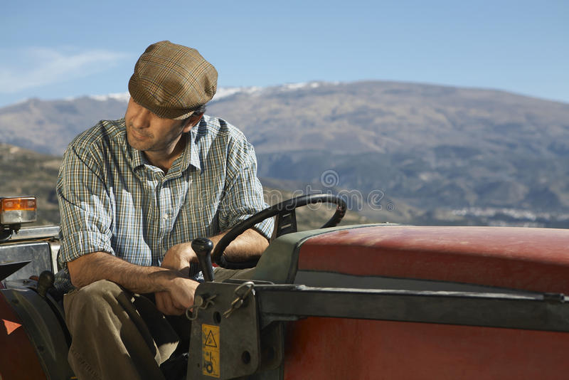 农夫坐拖拉机反对山 库存图片