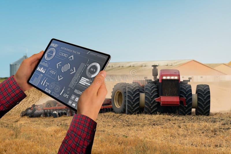 农夫控制一台自治拖拉机 免版税库存照片