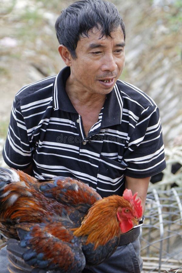 农夫显示他的一只在市场上的公鸡 免版税库存照片