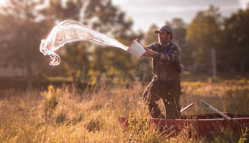 农夫渔夫委托从划艇的水 免版税库存图片