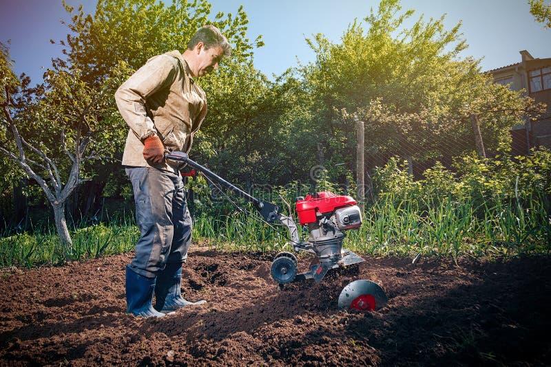 农夫犁有耕地机的土地,它为planti做准备 库存照片