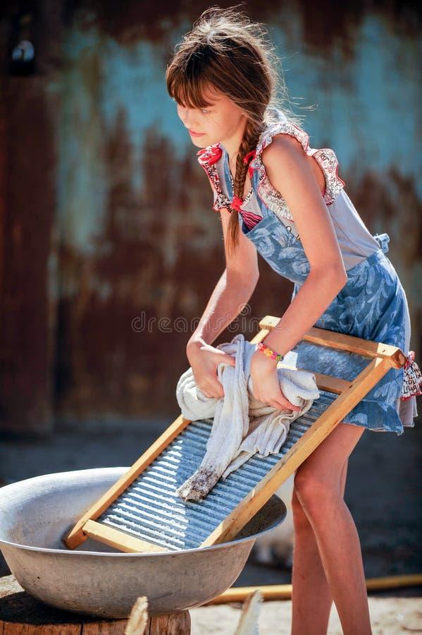 农夫` s女儿在围场洗涤他的父亲` s衬衣 库存照片