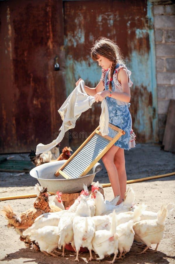 农夫` s女儿在围场洗涤他的父亲` s衬衣 免版税库存图片