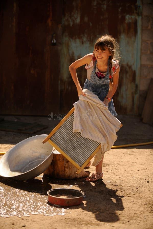 农夫` s女儿在庭院里洗涤他的父亲` s衬衣,包围由鸡 一个逗人喜爱的女孩是愉快,帮助的家庭 库存图片