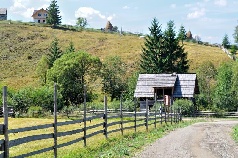 农村乡下公路篱芭风景、土路和木篱芭在村庄 免版税库存图片