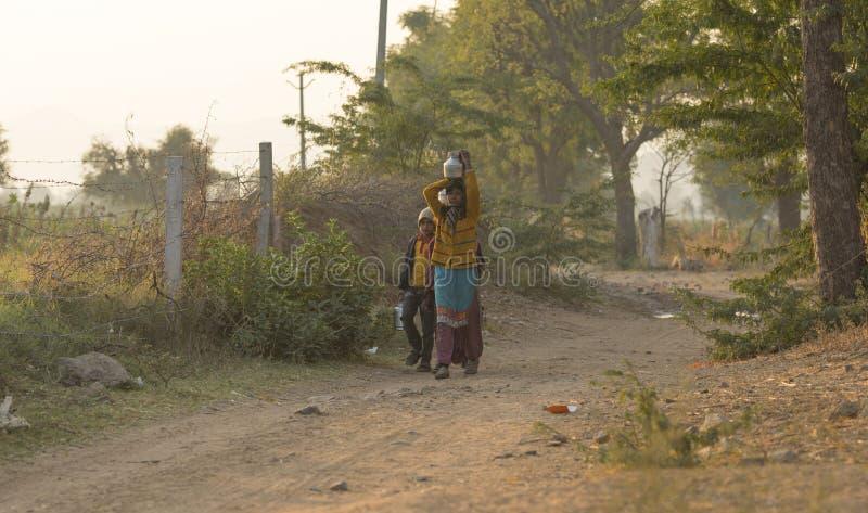 农村女孩运载水 免版税图库摄影