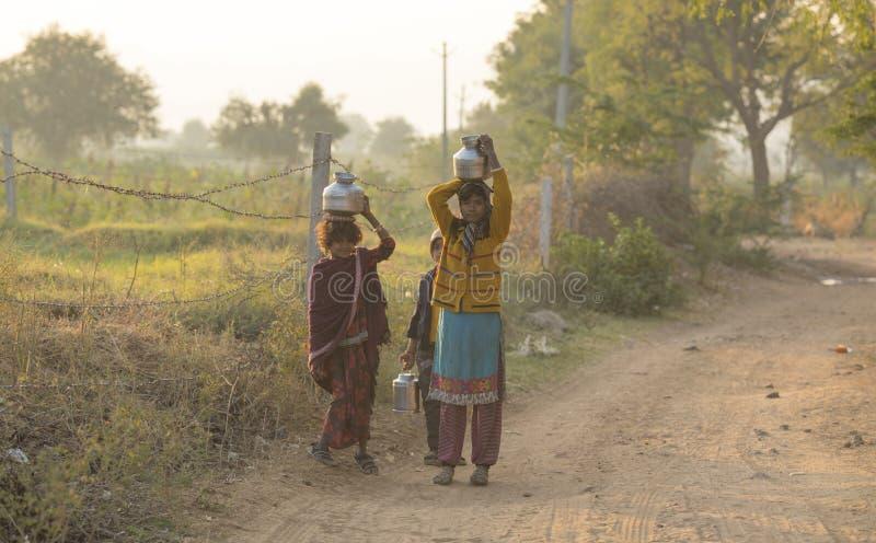农村女孩运载水 库存照片