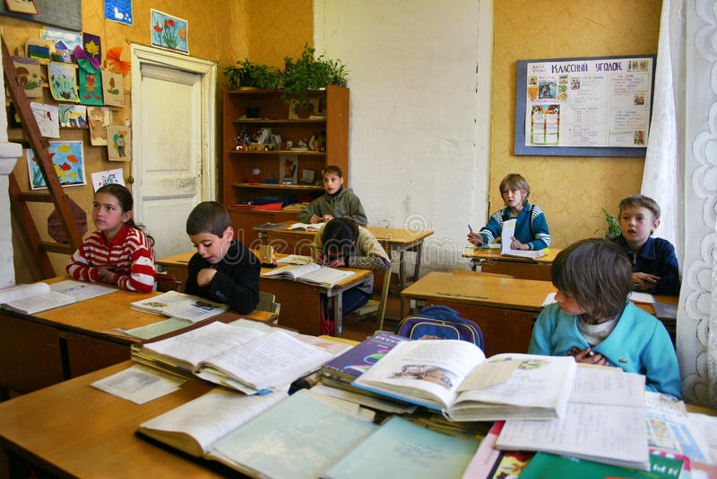 农村学校在乡下,学生坐在他们的在clas的书桌 库存图片