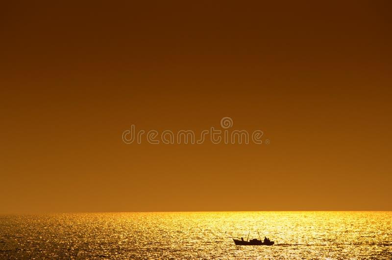 农村小船的渔夫在公海 日落树荫  库存图片