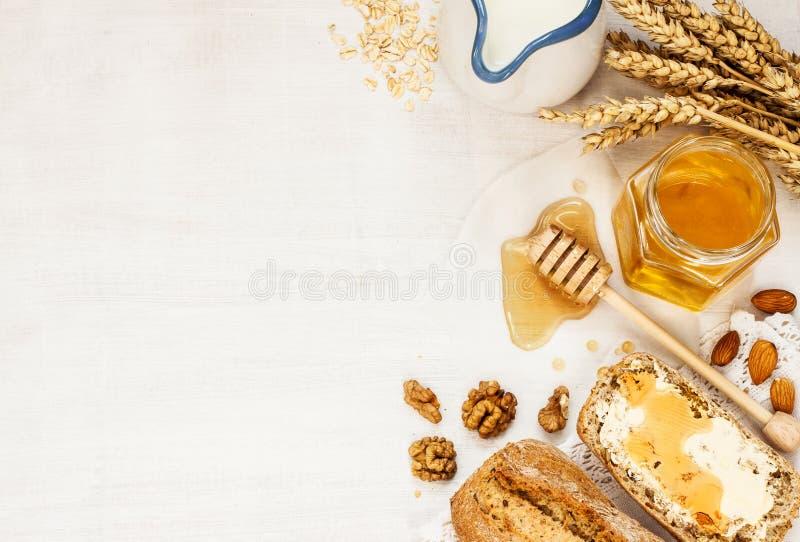 农村或国家早餐-小圆面包、蜂蜜瓶子和牛奶 图库摄影