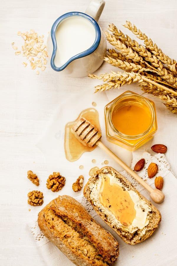 农村或国家早餐-小圆面包、蜂蜜瓶子和牛奶 免版税图库摄影