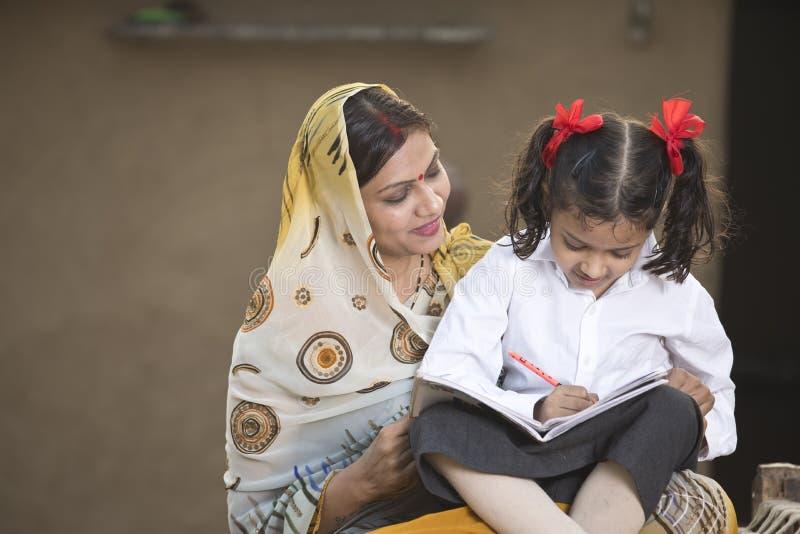农村有她的家庭作业的母亲帮助的女儿 免版税库存照片