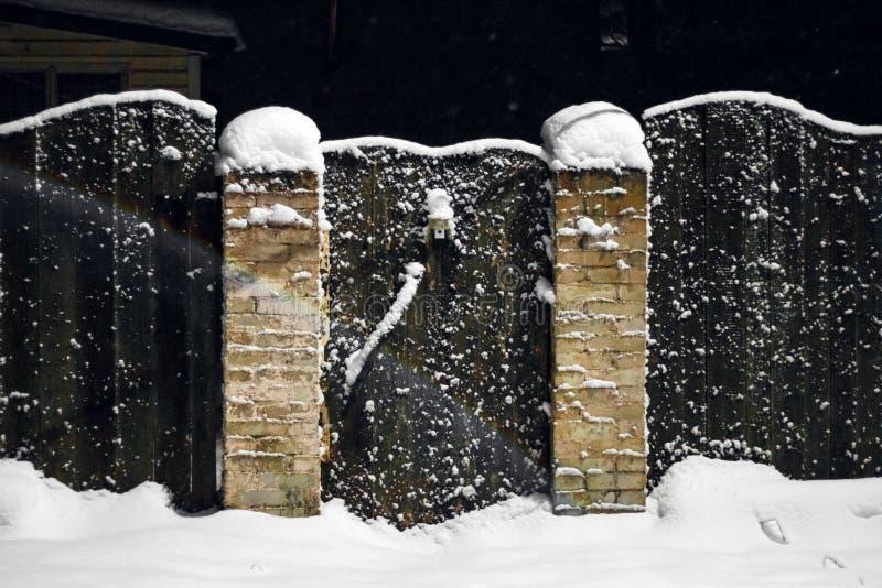 农村木篱芭在雪的冬天 免版税库存图片