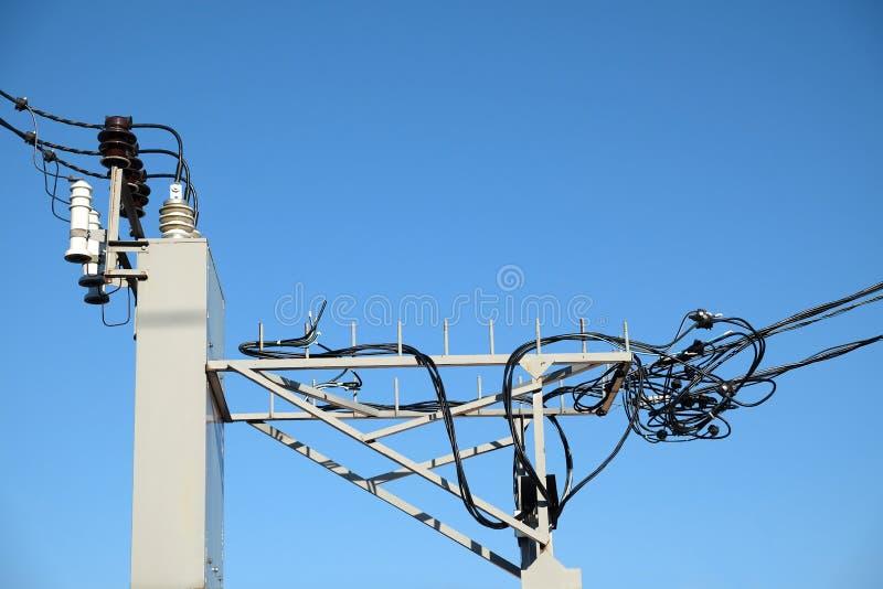 农村电源变压器的顶部有高压导线输电线的在清楚的无云的天空蔚蓝 图库摄影