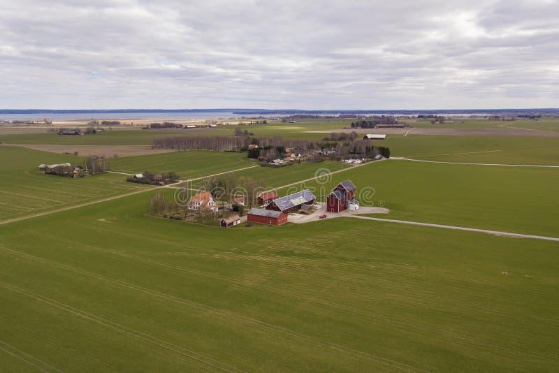 农村风景顶视图在晴朗的春日 有太阳照片流电盘区系统的农场在木大厦、谷仓或者房子 免版税库存图片