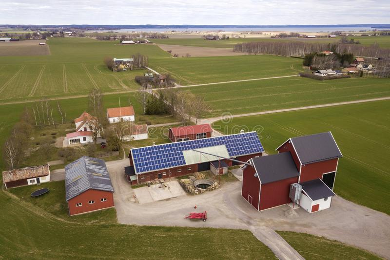 农村风景顶视图在晴朗的春日 有太阳照片流电盘区系统的农场在木大厦、谷仓或者房子 库存图片