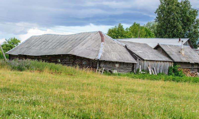 农村风景,一条村庄街道的后部有木柴和菜园的 老木房子和菜园 库存照片