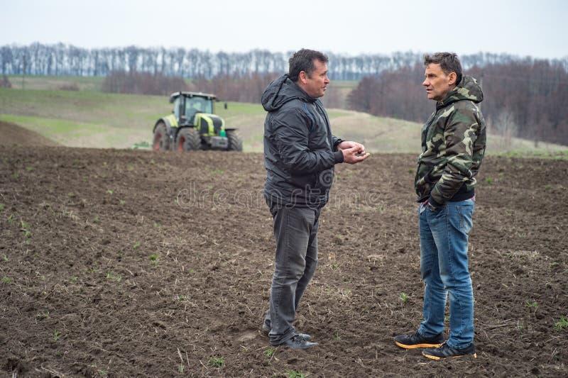 农艺师和农夫检查在播种的cer前的土壤湿气 库存图片